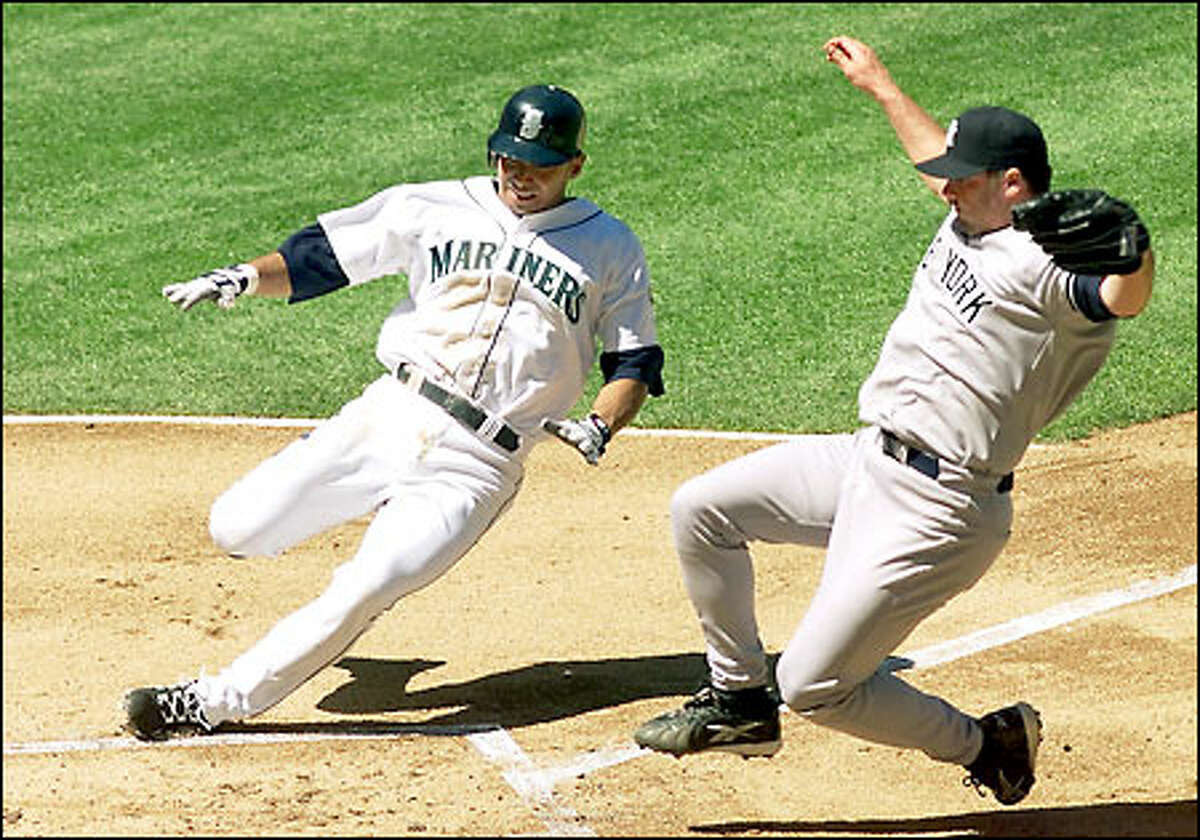 Carlos Guillen scores on a wild pitch by Yankees starter Roger Clemens, who raced to cover the plate in the second inning. The Mariners scored five runs in the first two innings against Clemens.