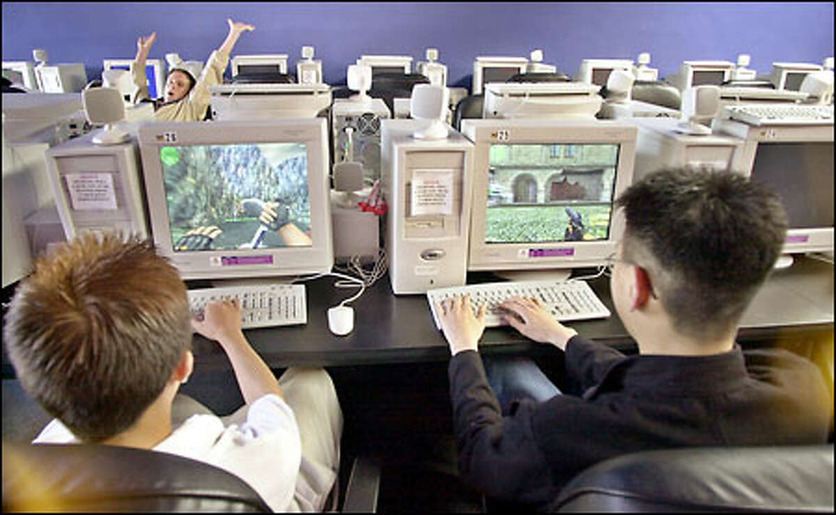 Darren Lau, 14, left, plays against his friend Benny Soo, 19, in the online game