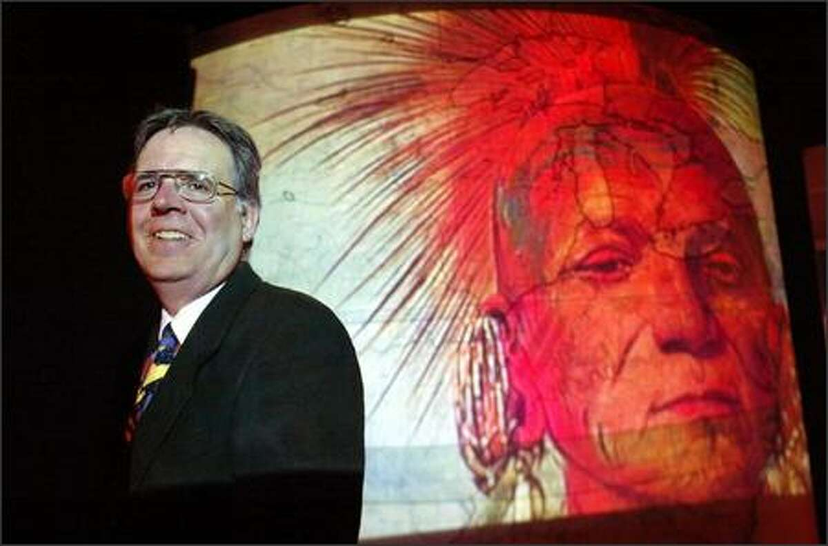 David Nicandri, director of the Washington State History Museum in Tacoma, with an image from a current exhibit,