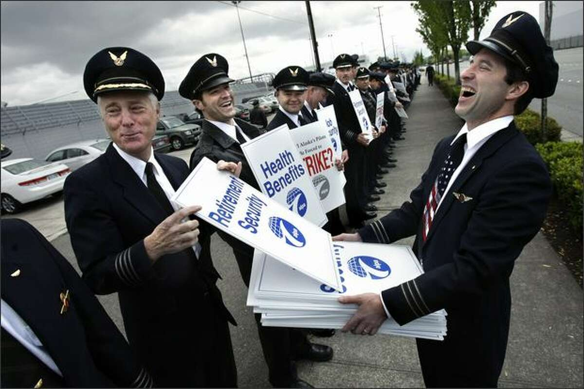 First Officer Brian Moynihan, right, reacts as Capt. Claude Tirman chooses a sign addressing retirement security during an informational picket of about 300 pilots Tuesday outside the Alaska Air Group shareholders meeting at the Museum of Flight. Tirman plans to retire Nov. 30.