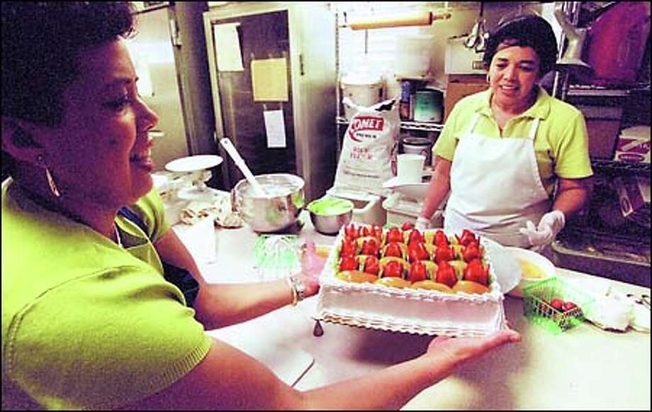 Ana Castro, far left, displays a pastel de tres leches just decorated with fruit by her sister, Aminta Elgin, at their Salvadorean Bakery in White Center. Photo: Dan DeLong, Seattle Post-Intelligencer / Seattle Post-Intelligencer