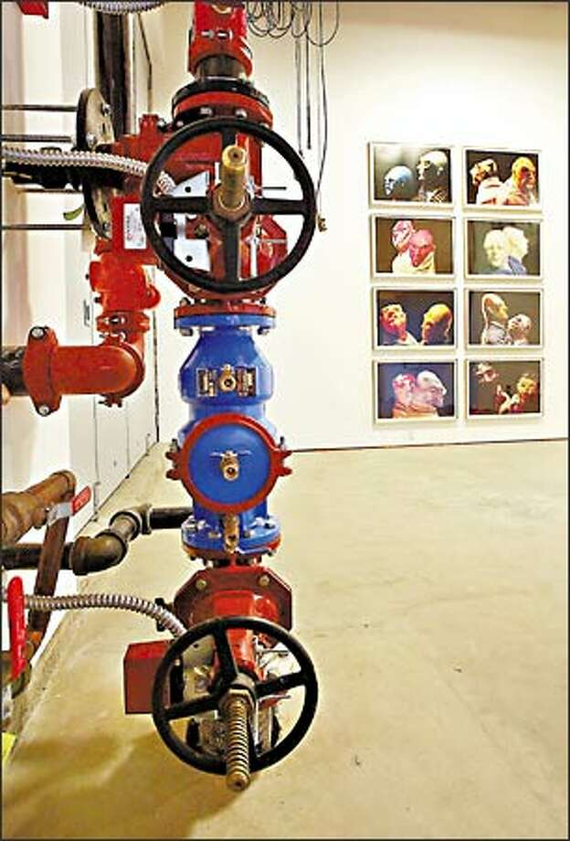 """German artist Thomas Schutte made grotesque clay figures, clothed them and then photographed them in pairs for """"United Enemies: A Play in 10 Parts."""" (The pipes and valves are part of the gallery's sprinkler system.) Photo: Mike Urban, Seattle Post-Intelligencer / Seattle Post-Intelligencer"""