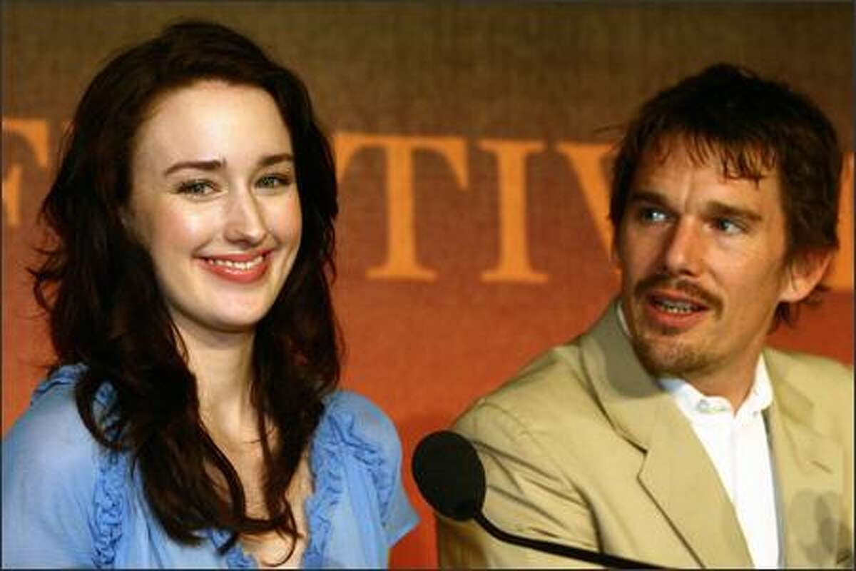 """Funny. She doesn't look like she's chowing down on jumbo-size french fries. Oh, wait. That's what the movie's trying to save us from. Here with Ethan Hawke, actress Ashley Johnson beams at the screening of """"Fast Food Nation"""" at the 59th International Film Festival in Cannes, France. Fast-food producers are nervous. They fear we'll think we can look like Johnson if we trade our Big Macs for carrots. Just how dumb do they think we are? (LAURENT EMMANUEL/AP)"""