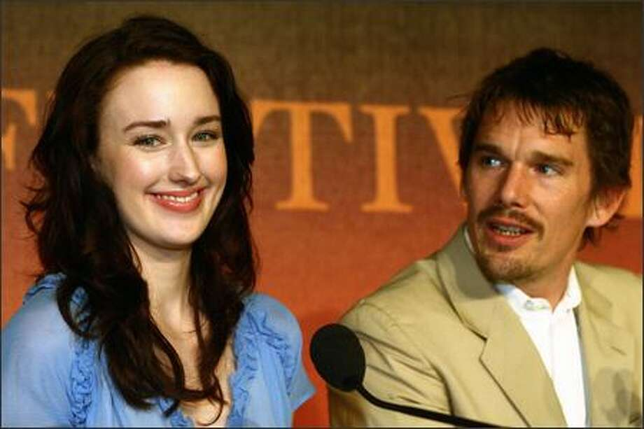 "Funny. She doesn't look like she's chowing down on jumbo-size french fries. Oh, wait. That's what the movie's trying to save us from. Here with Ethan Hawke, actress Ashley Johnson beams at the screening of ""Fast Food Nation"" at the 59th International Film Festival in Cannes, France. Fast-food producers are nervous. They fear we'll think we can look like Johnson if we trade our Big Macs for carrots. Just how dumb do they think we are? (LAURENT EMMANUEL/AP) Photo: Associated Press / Associated Press"