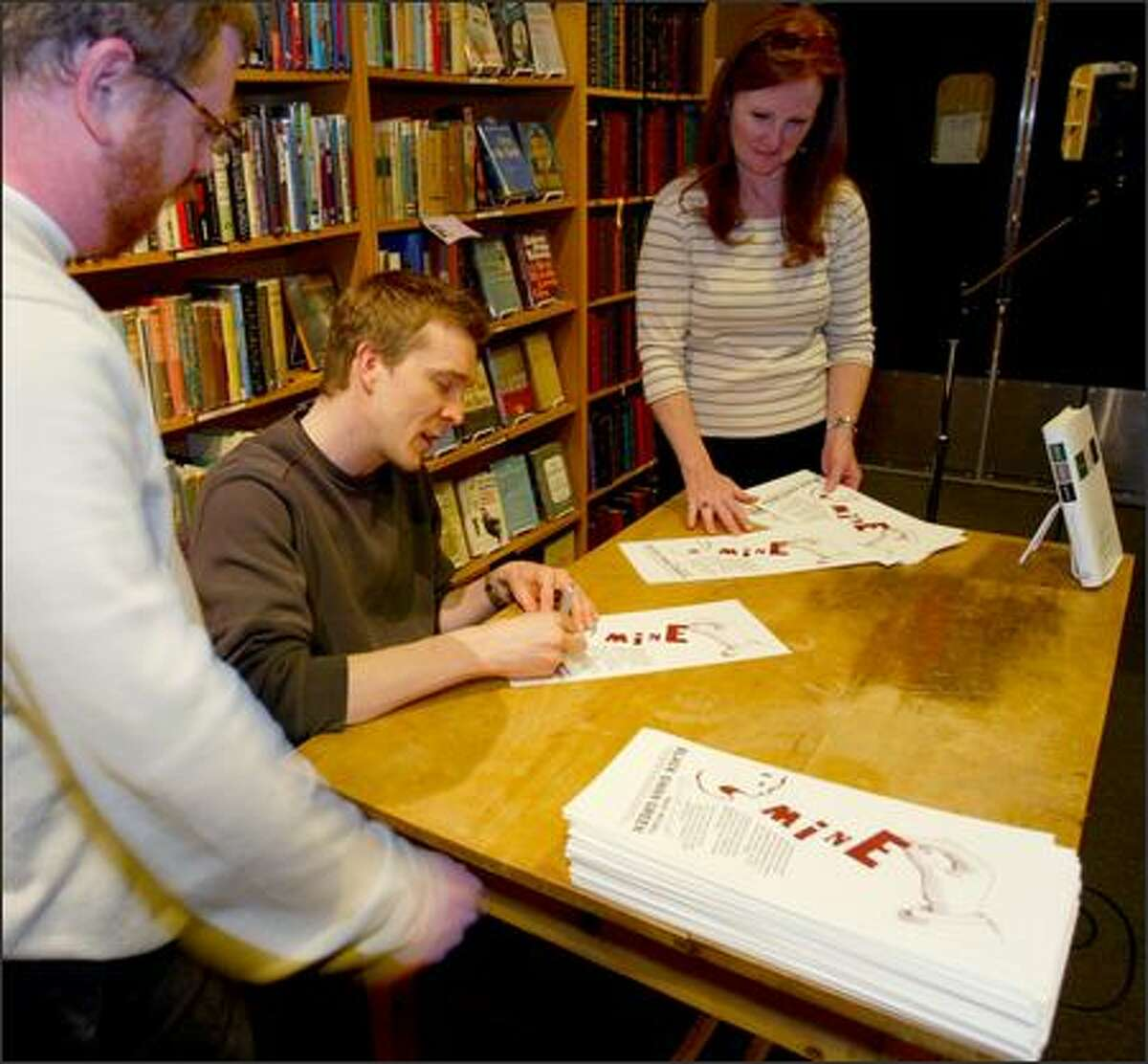 """""""Black Swan Green"""" author David Mitchell signs broadsides at Third Place Books April 26. With him are store managing partner Robert Sindelar, left, who had the idea for the broadsides, and Gail DiRe, the author's escort."""