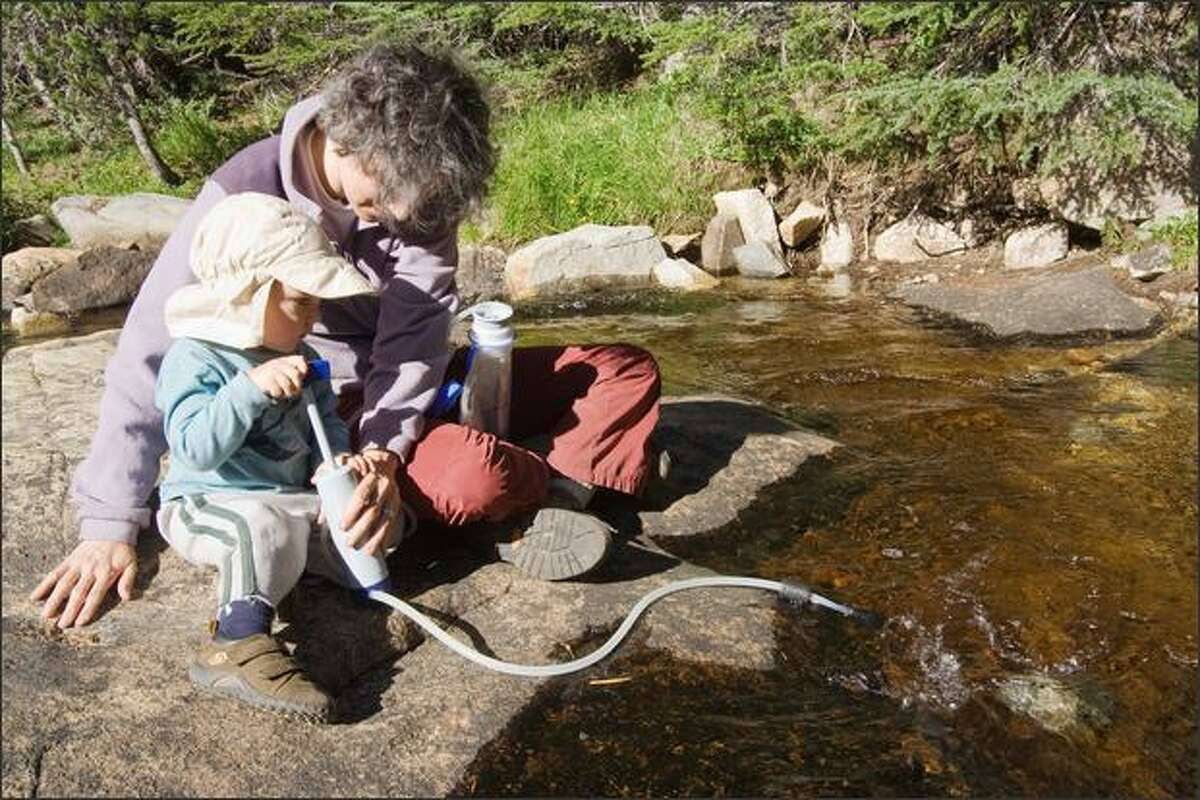 Rachel Konrad lets Levi participate in pumping water through a purifier.