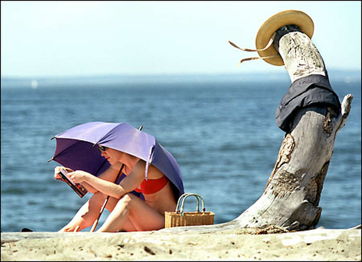 Emily Etie of Belltown enjoys the warm weather yesterday at Alki Beach.