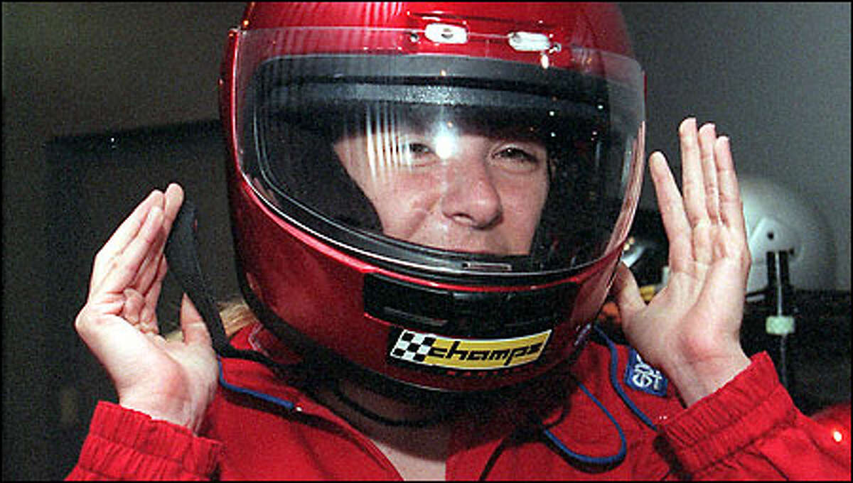 Becky Weiss, a software developer at Microsoft, dons a protective helmet for an afternoon'sr acing at Champs Karting in Redmond.