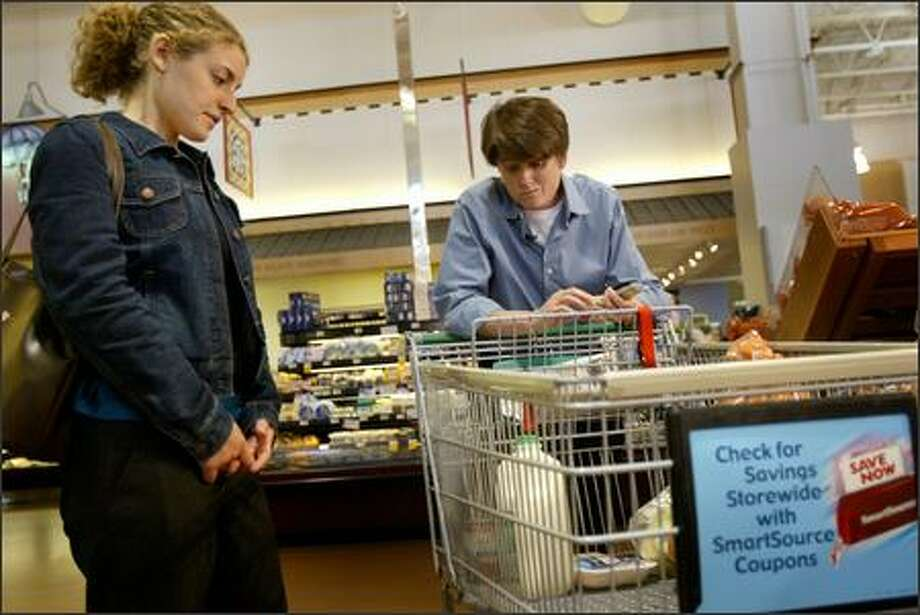 Claire West, left, who works for Food Lifeline, helps Sally Clark, a Seattle city councilwoman, as she tries to buy a week's worth of groceries for $21 -- or $1 a meal -- Tuesday at Fred Meyer in Ballard. Photo: Joshua Trujillo, Seattlepi.com / seattlepi.com