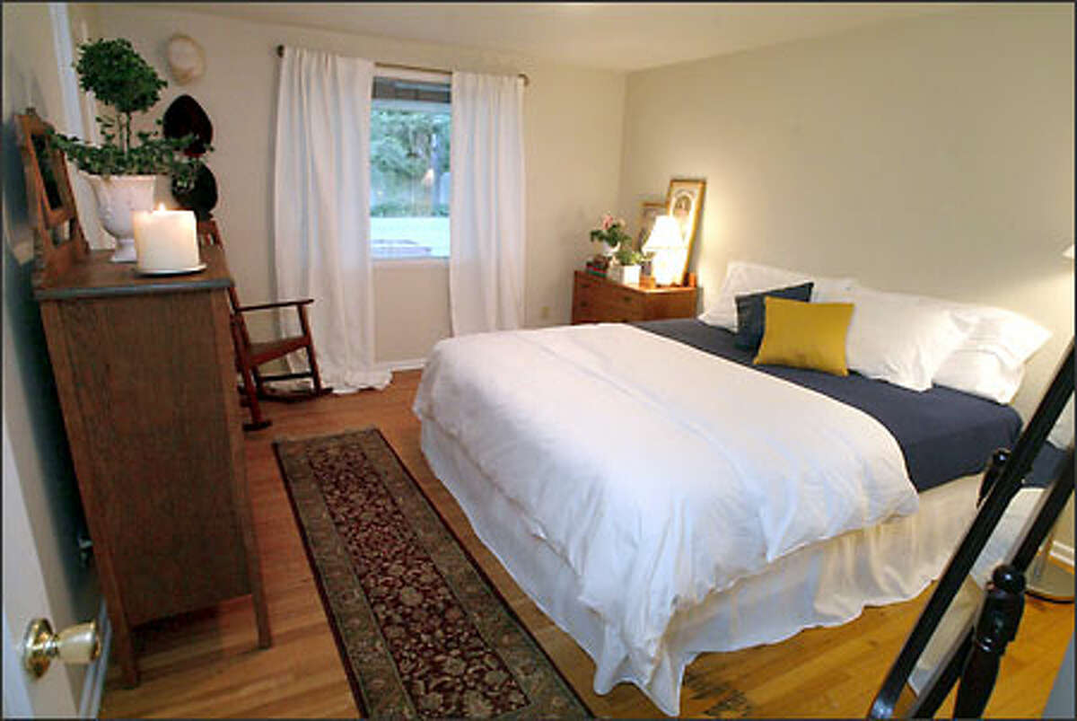 Two days later, the bedroom is airy and light, even though it has more furniture in it. The differences? Beige paint on the walls; a new standing lamp; flowing white curtains; new white duvet, bed skirt and pillowcases; a rocking chair moved from another room; and wall pictures remove
