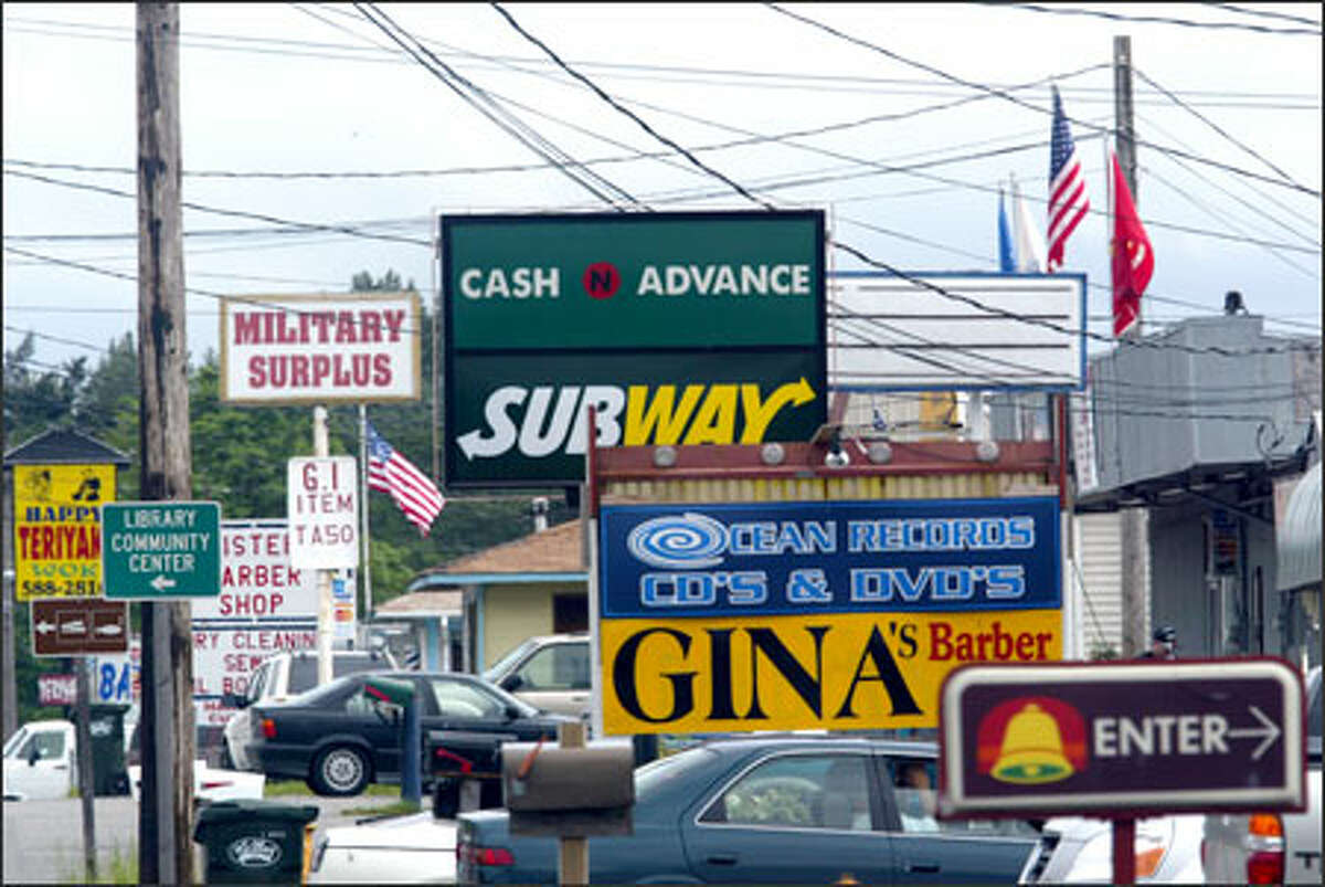 The clutter of signs along a street in Tillicum outside Fort Lewis includes one drawing attention to a cash-advance store.
