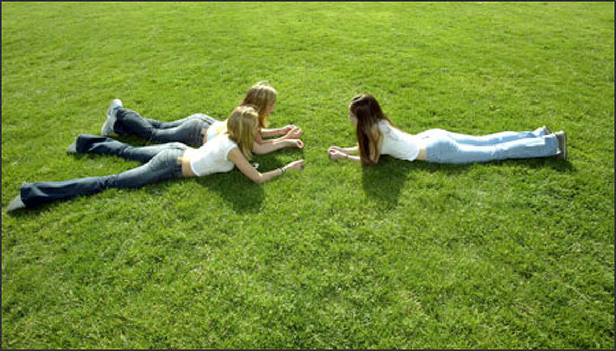 Whitman Middle School students, clockwise, from right: Shelby Kruse, Sara Yates and Kelsi Thorpe, all 14, favor the grass at Loyal Heights Playfield over artificial turf.