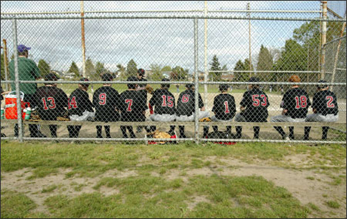 Members of the Ida Culver House Little League team wait for their game with Weber Law to begin at Loyal Heights Playfield. Weber Law games have been rained out four times this year, and some parents said they hope synthetic turf will mean less-muddy fields and more time spent playing ball.