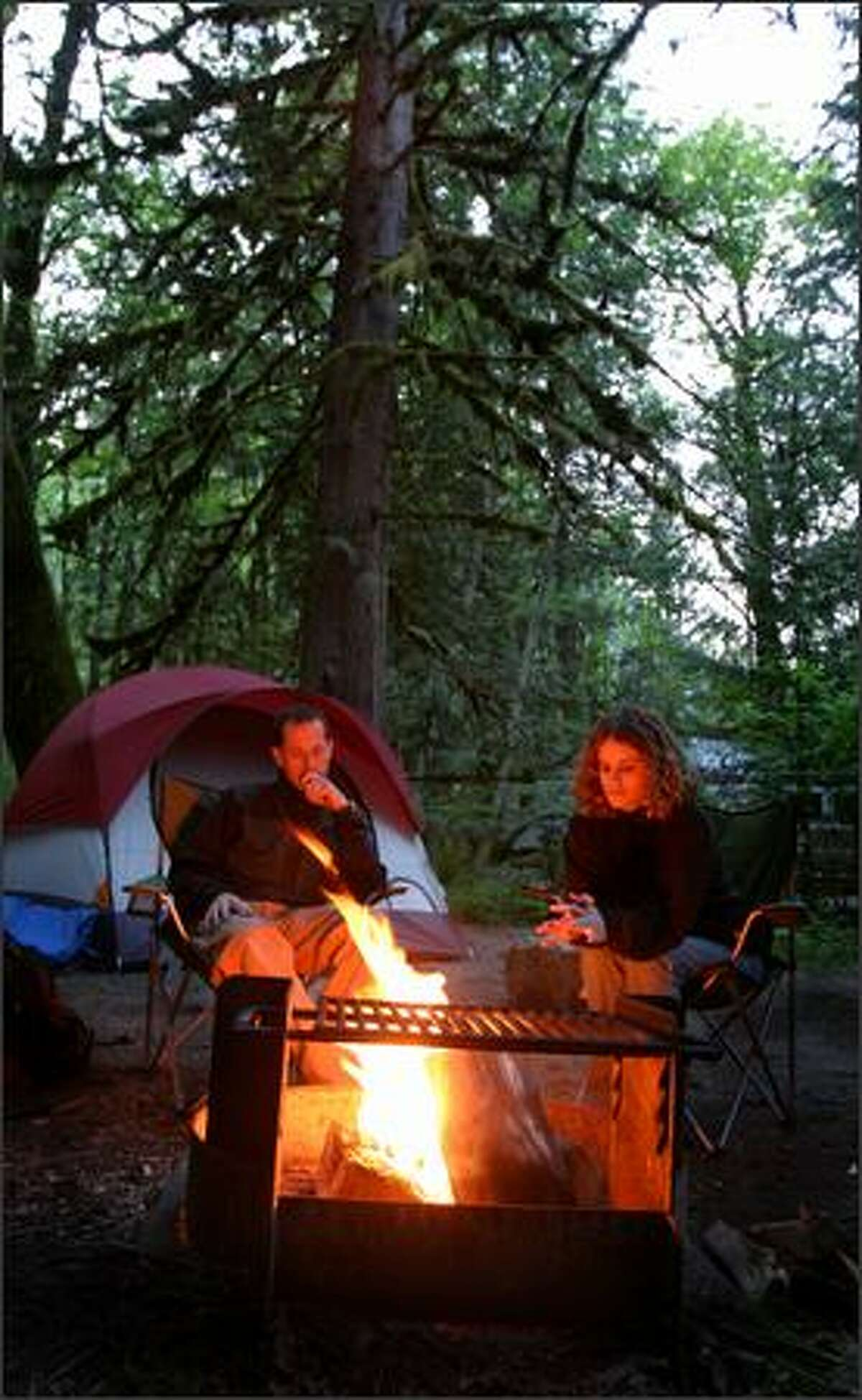 Whatcom County residents Craig and Jenna Lunde gaze into their campfire at Goodell Creek Campground. Usually, demand for the campsites is limited, but damage to Mount Rainier National Park and the closure of Rockport State Park may change that this year.