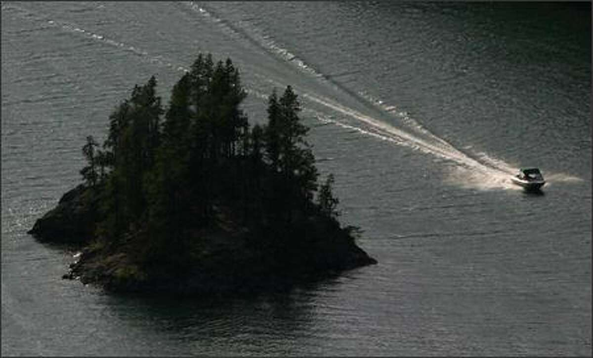 A boat speeds across Ross Lake, one of more than 300 lakes and ponds in North Cascades National Park.