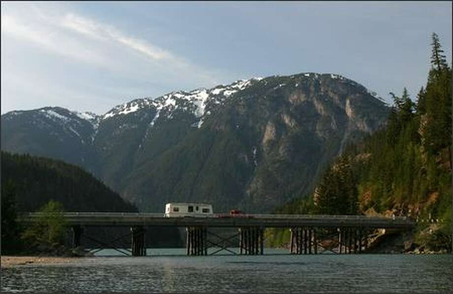 A truck tows a camper across Diablo Lake on state Route 20, which offers a lovely scenic view. There are more than half-million acres, filled with rugged, remote peaks and towering old-growth forests in North Cascades National Park. Photo: Joshua Trujillo, Seattlepi.com / seattlepi.com