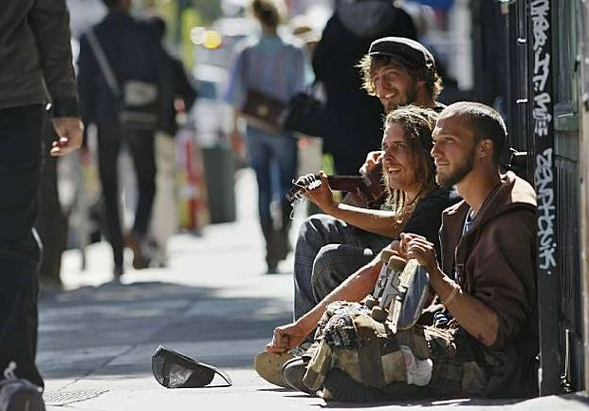 Peter Barker, 24 (playing guitar), Michael Cook, 23 (center), and Aarron West, 22, hang out on Haight Street in San Francisco on Saturday. A measure being proposed for November's ballot would ban sitting or lying on the city's sidewalks.