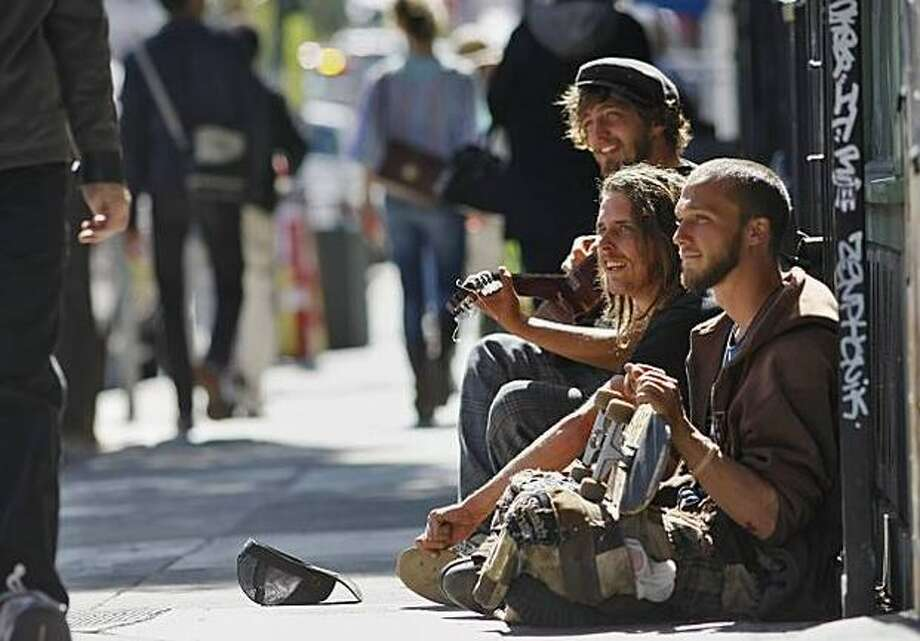 Peter Barker, 24 (playing guitar), Michael Cook, 23 (center), and Aarron West, 22, hang out on Haight Street in San Francisco on Saturday. A measure being proposed for November's ballot would ban sitting or lying on the city's sidewalks. Photo: San Francisco Chronicle / San Francisco Chronicle