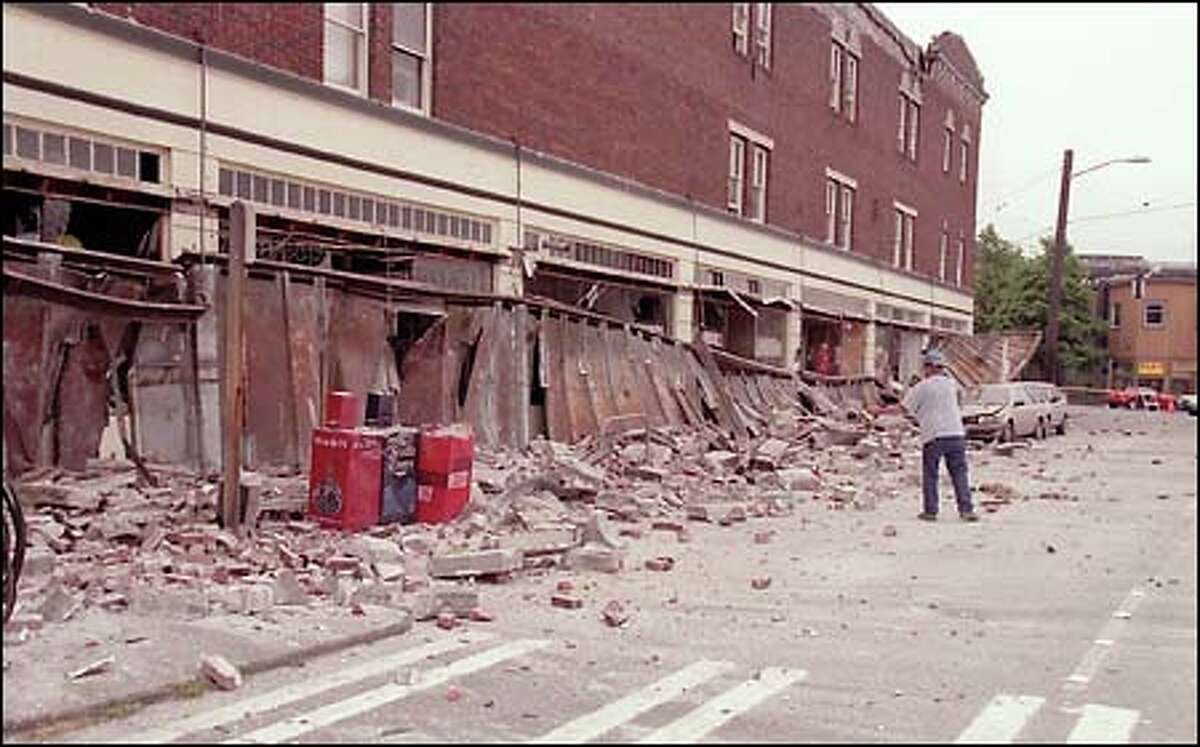 A worker helps clean up bricks after the facade fell from a building in Fremont. Several storefronts were heavily damaged, and parked cars were crushed.