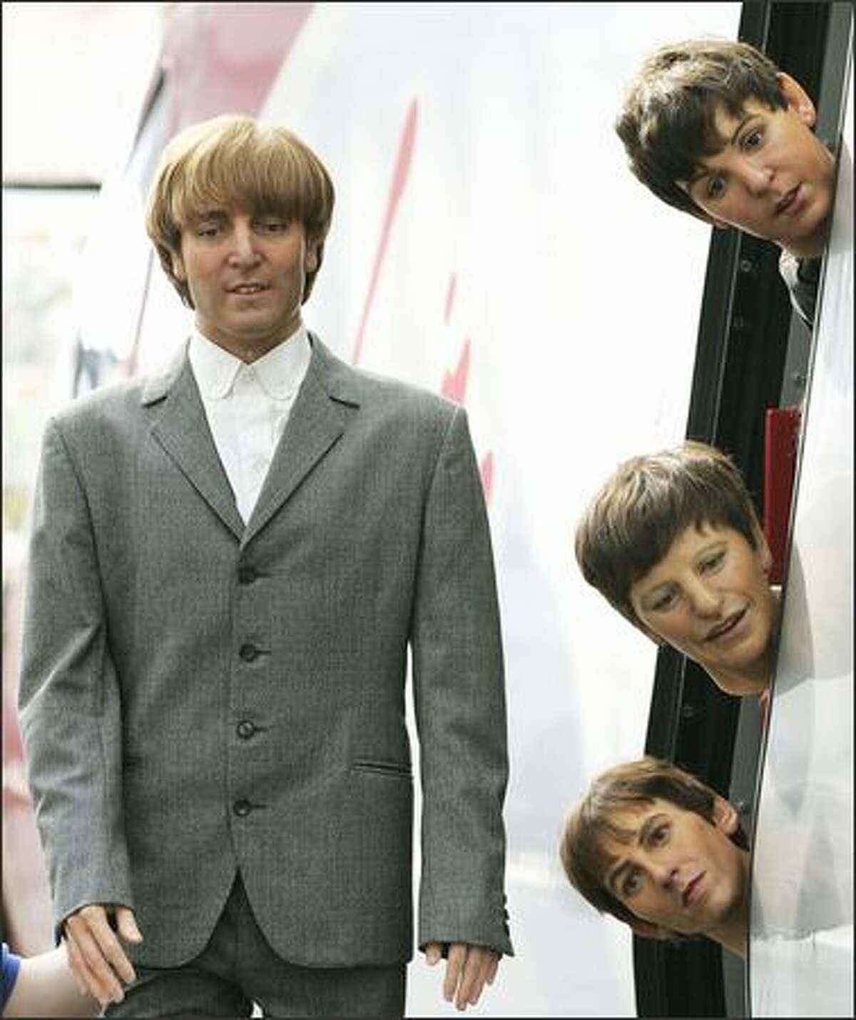 It's a long and winding road to becoming a creepy waxwork. The Beatles -- John Lennon, left, and Paul McCartney, top, Ringo Starr and George Harrison, being held from the door of a train, are heading for the Beatles Story Museum in Liverpool, England. They previously had been on display at Madame Tussauds in London.