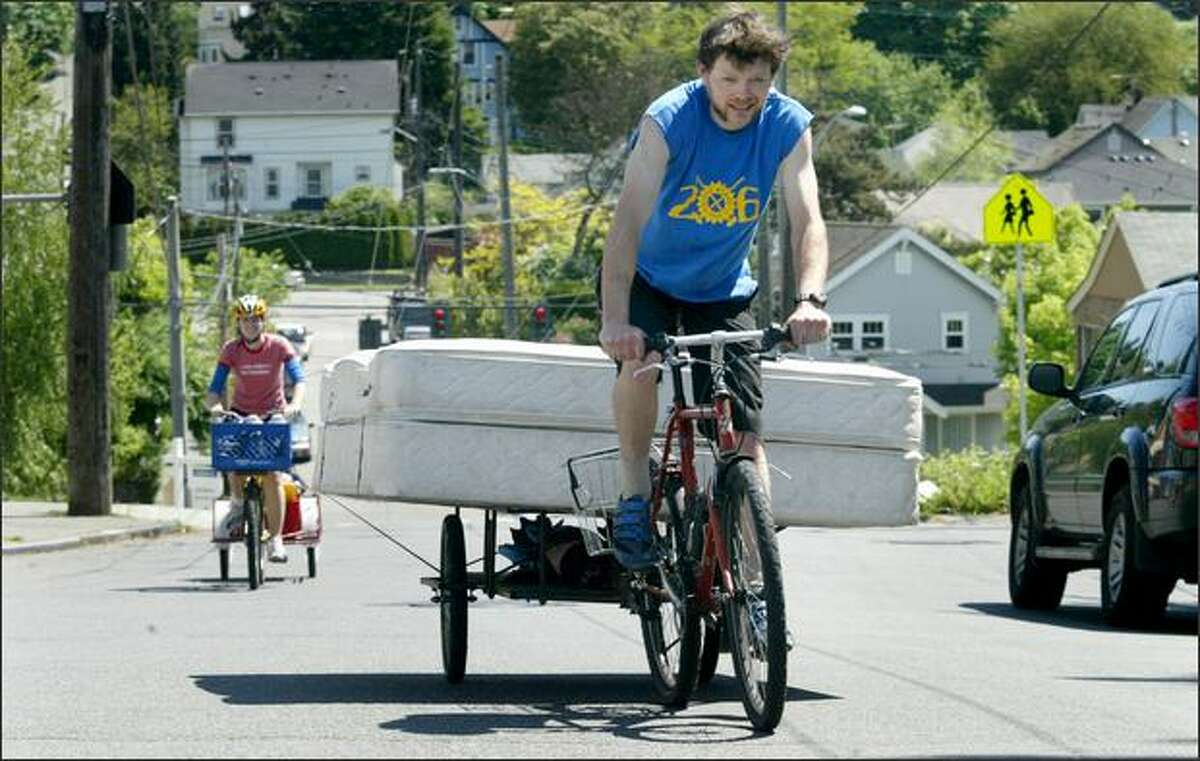 """Colin Stevens of Seattle uses his bicycle and cart to pull a queen-size mattress up a hill while helping friends Joe Goldberg and Venessa Brown make a """"zero-carbon"""" move in Seattle on Saturday. Chris Eggermont (left) of New York, also a friend of the couple, transports more of their belongings."""