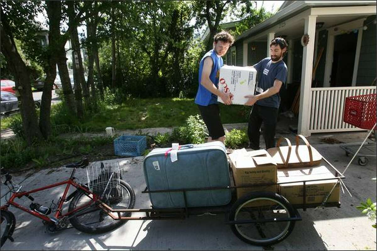 Joe Goldberg (right) gets help from Colin Stevens to load Stevens' bike cart during the move.