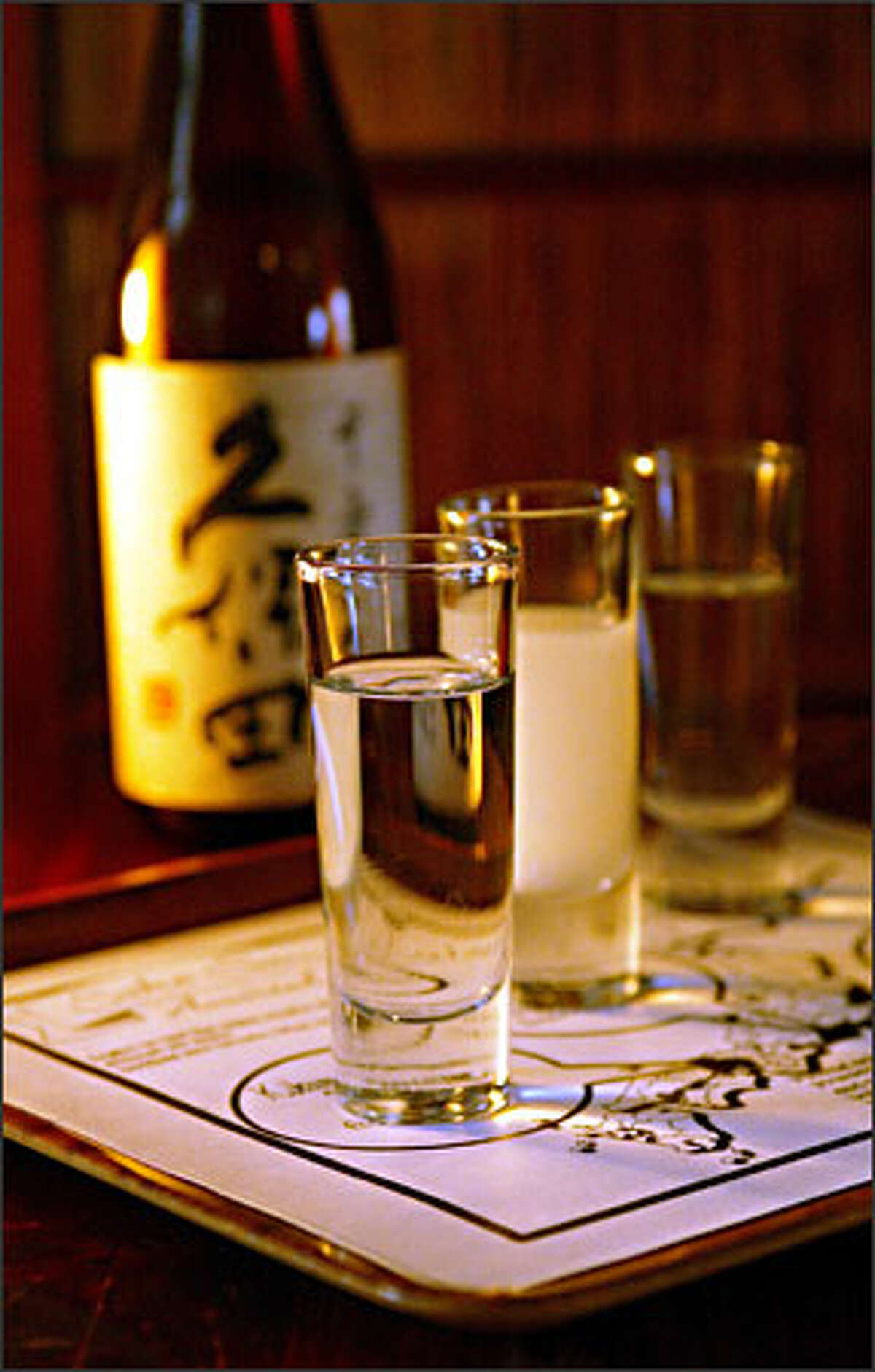 A sampler of, from left, taru, nigori and daiginjo sakes is served on a tray with a map of Japan that points out the brews' regions of origin.