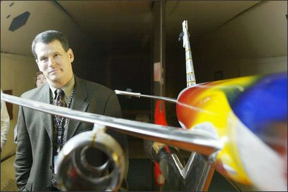 Tom Cogan, chief project engineer for Boeing's 7E7 program, pauses by a model of the 7E7 Dreamliner after it went though testing yesterday at Boeing's high-speed wind-tunnel facility off East Marginal Way across from Boeing Field. The plane is set to enter service in the first half of 2008.
