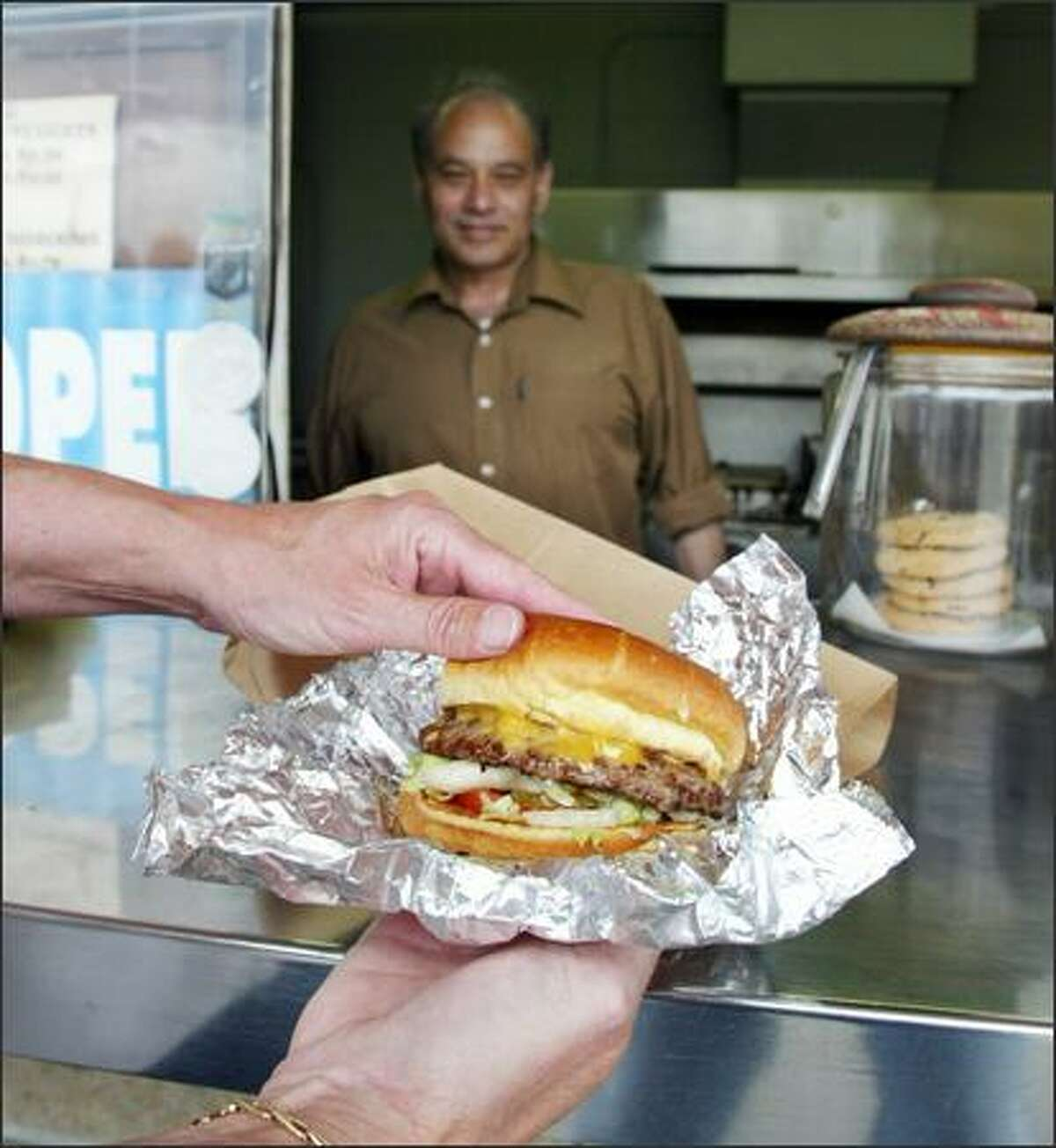 A customer checks out her cheddar burger at Gordo's, run by Paul Sharma (pictured) and his family.