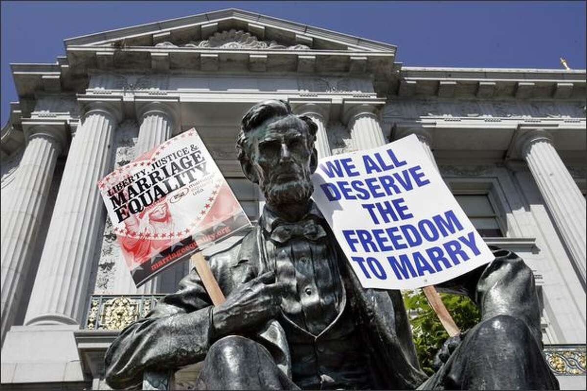 Demonstrators placed signs on a statue of President Abraham Lincoln in front of San Francisco City Hall after the California State Supreme Courtupheld on Tuesday a voter-approved ban on gay. (AP Photo/Paul Sakuma)