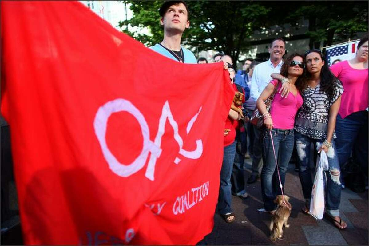 Galina Medvedeva, background left, and her girlfriend Fatimah Bahandari listen to a speech as Eli Steffen holds a red Queer Coalition flag on Tuesday, May 26, 2009 at Westlake Park in Seattle during a rally against the court ruling in California that upheld proposition 8, banning gay marriage in California.