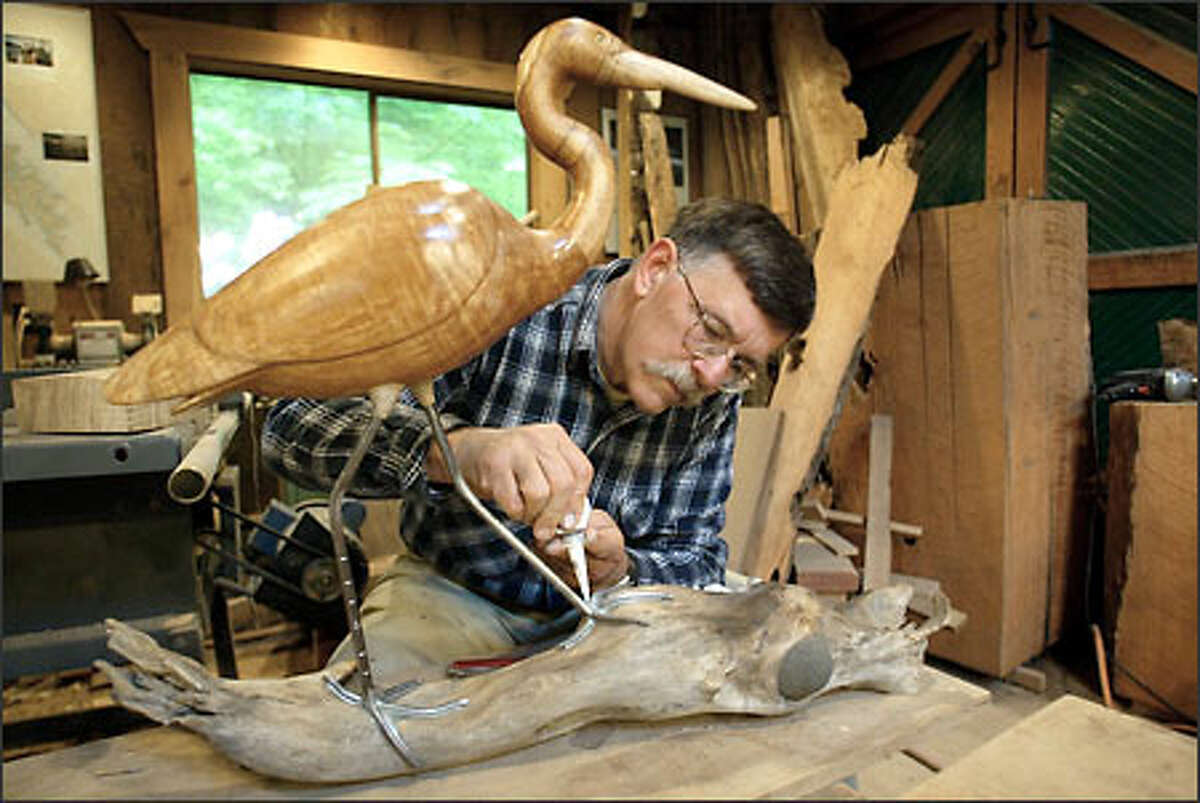 Rand Jack, who is retiring from teaching at Western Washington University, works on a great blue heron he carved of local maple.