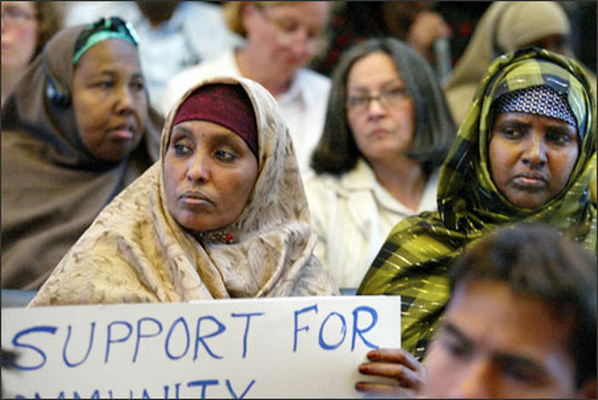Sirad Khaalir, center with sign, and other members of Seattle's refugee communities attend a City Council forum.