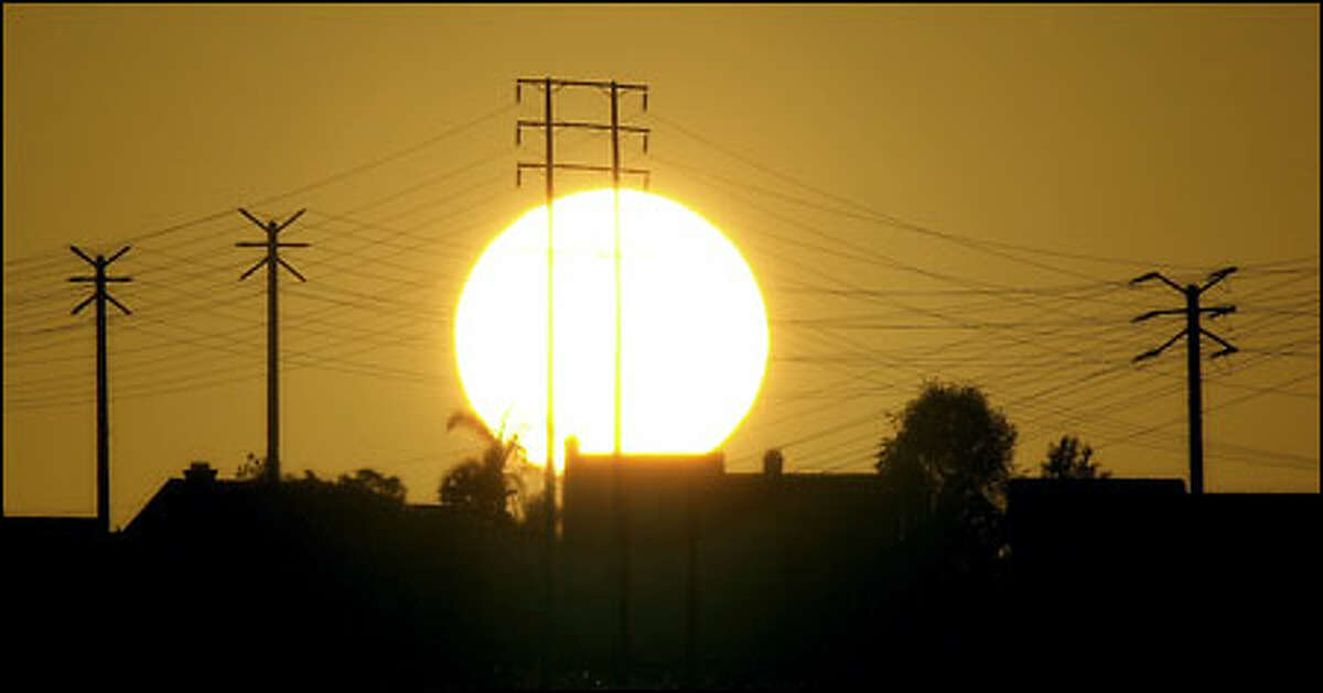 The sun setting behind high-tension transmission lines in Moorpark, Calif., illustrates the problems faced by that state even as an unsympathetic President Bush prepares to visit.