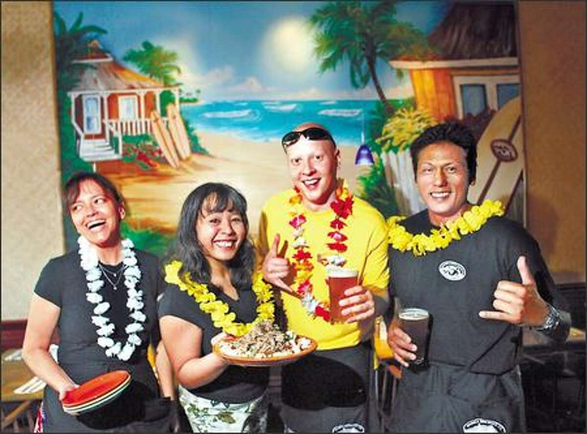 Waimea Brewing Company employees, wearing festive leis, help establish the Hawaiian atmosphere. From left are Jackie McDerrmott, Rosie Ruiz, Kurt Grittman and Brian Ebanez.