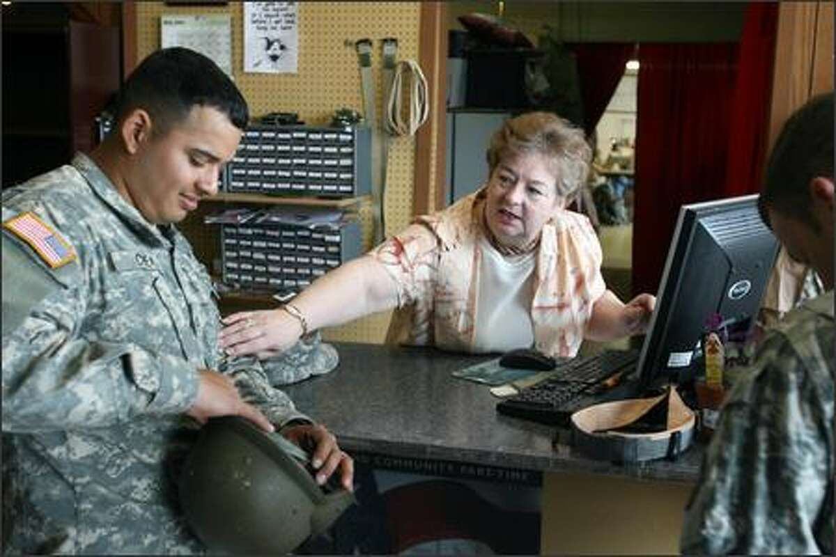Tavie Smith reaches out to Henry Chea, who was visiting Gaey Specialties and Awards Inc. for some additions to his uniform. The shop near Fort Lewis is well-versed in the military's exacting uniform regulations and is known for its caring service.
