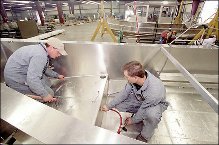 Chris Archambeau and Jeremy Boyd work on a Coast Guard Homeland Security vessel being built by Safe Boats International in Port Orchard. Photo: Phil H. Webber, Seattle Post-Intelligencer / Seattle Post-Intelligencer