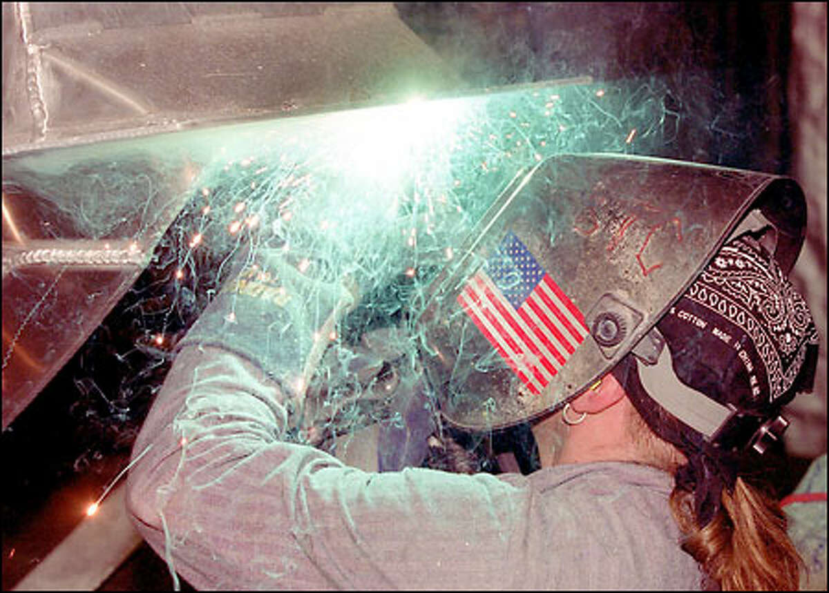 John Swann, a welder for Safe Boats International, works on the bottom of the vessel. Safe Boats' largest customer is the Coast Guard, for which it builds so-called non-standard boats.