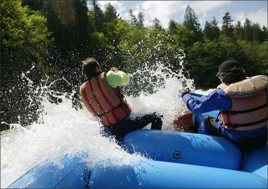 Jerry Michalec, right, and fellow North Cascades guide Guy Cooper catch a wave in the Skagit River rapids. Photo: Mike Kane, Seattle Post-Intelligencer / Seattle Post-Intelligencer