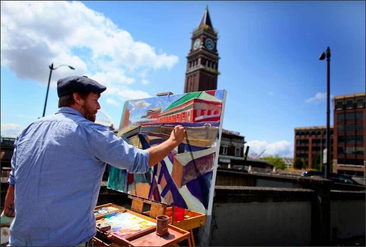 Artist Ethan Jack Harrington paints a scene of the King Street Station in Seattle's International District. Harrington, who paints surreal cityscapes and sultry portraits, said he has painted scenes of the downtown building about 20 times. This time, however, he decided to leave out the landmark's most identifying feature - its signature clock tower.