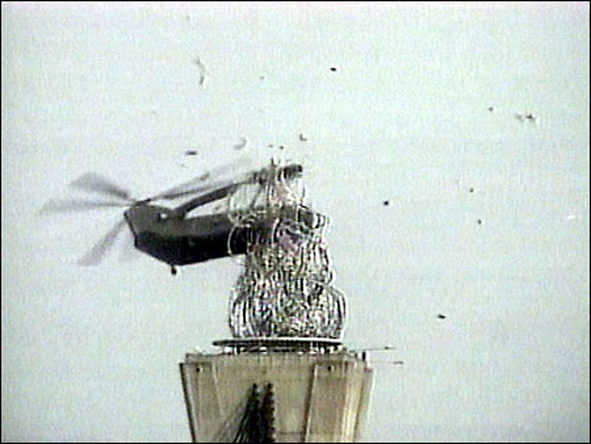 A South Korean army CH-47 Chinook helicopter begins to break up after striking a giant sculpture shortly after lowering it onto a plinth above a road bridge in Seoul. The three crewmen were killed yesterday after the rotors clipped the statue and the bridge tower, snapping the copter in two. One half fell onto the bridge, the other half into the Han River. Army scuba divers were working to recover the wreckage. This image was taken from television.