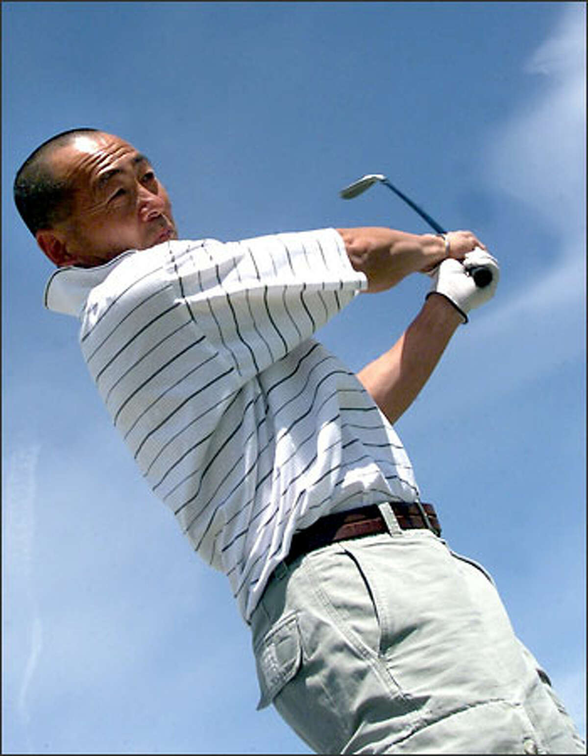 Scott Oki follows through on a golf shot.