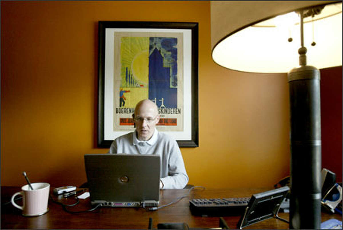 Henri Broekmate, senior vice president of Lionbridge Technologies Inc., works at his home office in Sammamish. He uses several gadgets to stay connected.