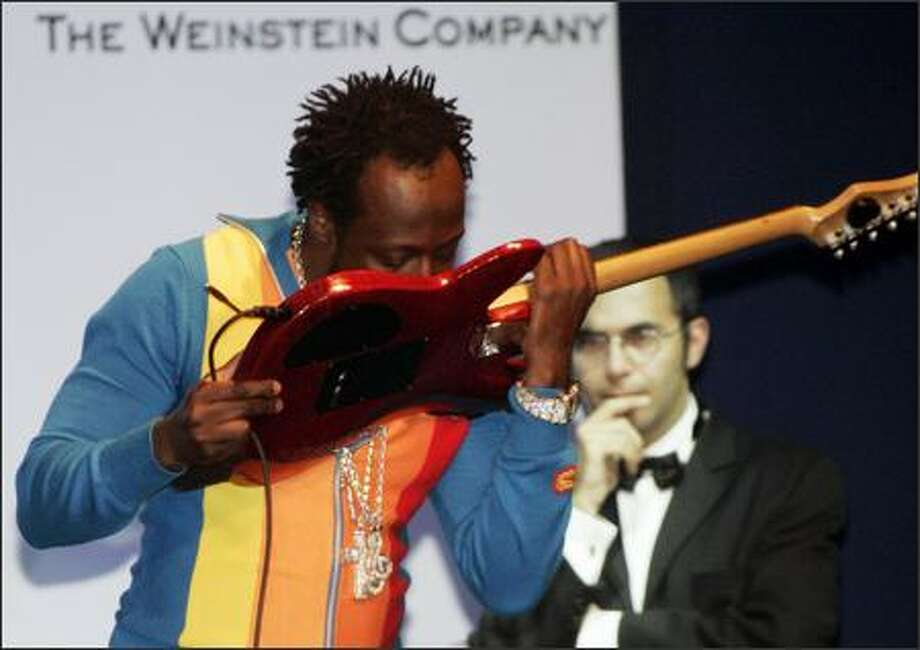 Wyclef Jean is not trying to eat that guitar, but he is trying to pull off a Jimi Hendrix. But, honestly, it looked so much better when Thaddeus Turner of Maktub did it at Bumbershoot last year. Here Wyclef tries it at amfAR's Cinema Against AIDS 2006 during the Cannes Film Festival. (JEFF CHRISTENSEN / AP) Photo: Associated Press / Associated Press