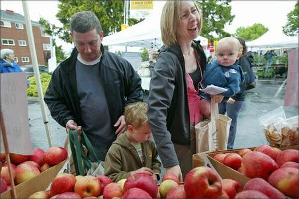 Nick Wiley, Kathleen Whitson and their two sons, Clayton, 4, and Joey Wiley, 1, choose among apples from Tiny's Organics at the West Seattle Farmers Market.