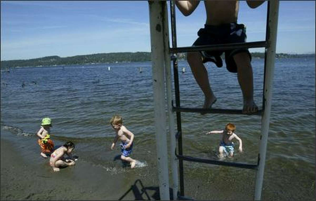 Kaden Pleas, 4, climbs down from a lifeguard tower as Julian Cummings, 2, left, Mirella Ryser, 5, Nikola Kasarskis, 3, and Aidan Cummings, 3, take advantage of the weather Tuesday by playing at Matthews Beach in the Sand Point area of Seattle.