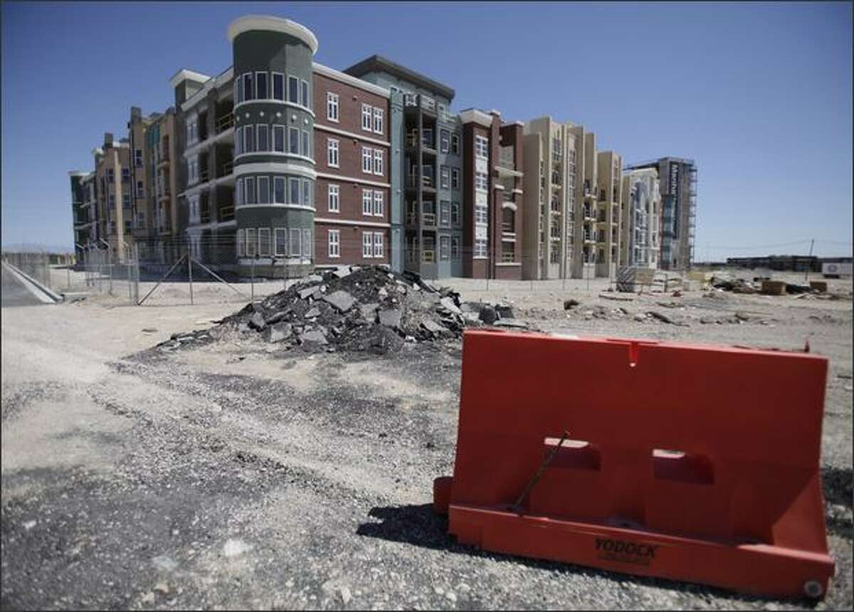 In this May 8, 2009 file photo, Manhattan West, a stalled condominium project, stands unfinished behind a fence in Las Vegas. (AP Photo/Jae C. Hong, File)