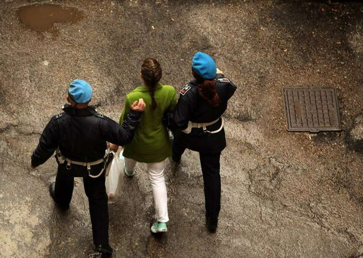 Defendant Amanda Knox (center) is escorted away from court at the end of the final day of the Meredith Kercher murder trial on Dec. 4, 2009 in Perugia, Italy.