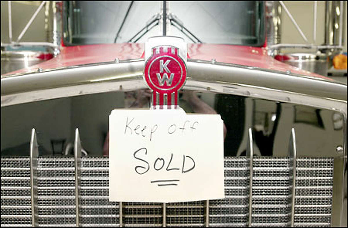 A sold sign hangs over the massive grille of a 2002 Kenworth W-9 diesel truck on display yesterday in a Markham, Ill., showroom.