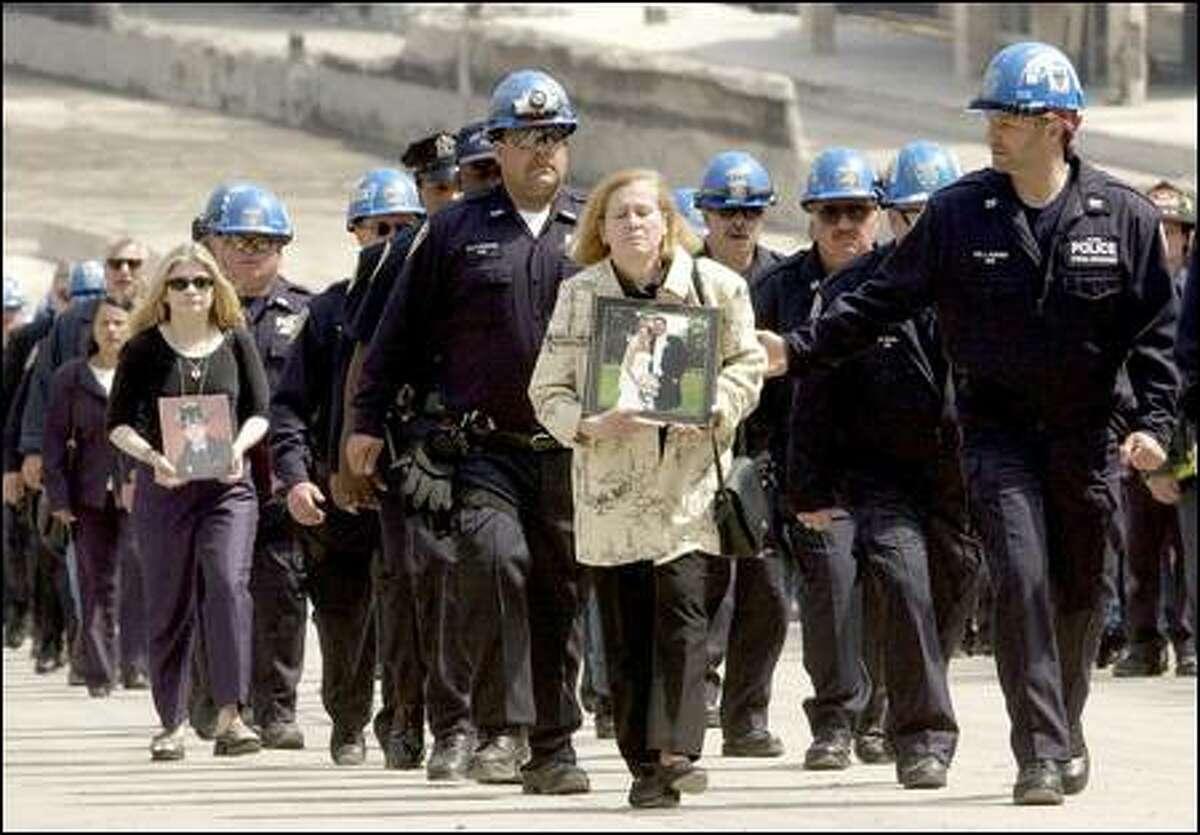 Authority Police march from ground zero with Maria Sanpio, right, and Christina Regenhard, second from left, holding photos of family members who died.